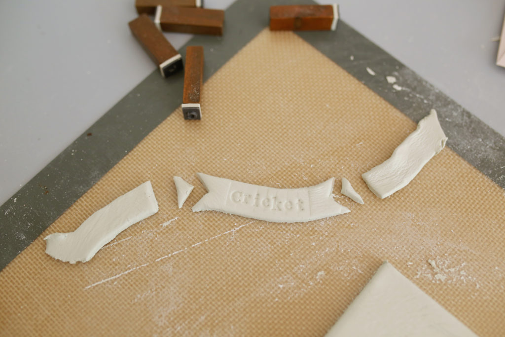 Step 6 of a DIY clay handprint: emboss your child's name with stamps and cut out a pennant shape